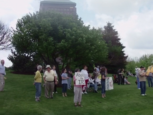 Dozens of protesters seek shade under a nearby tree while waving at honking cars.
